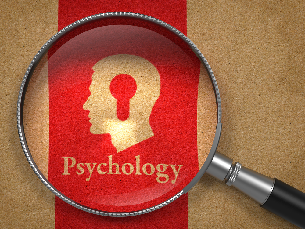 Psychology Concept Magnifying Glass with Word Psychology and Icon of Head with a Keyhole on Old Paper with Red Vertical Line Background.